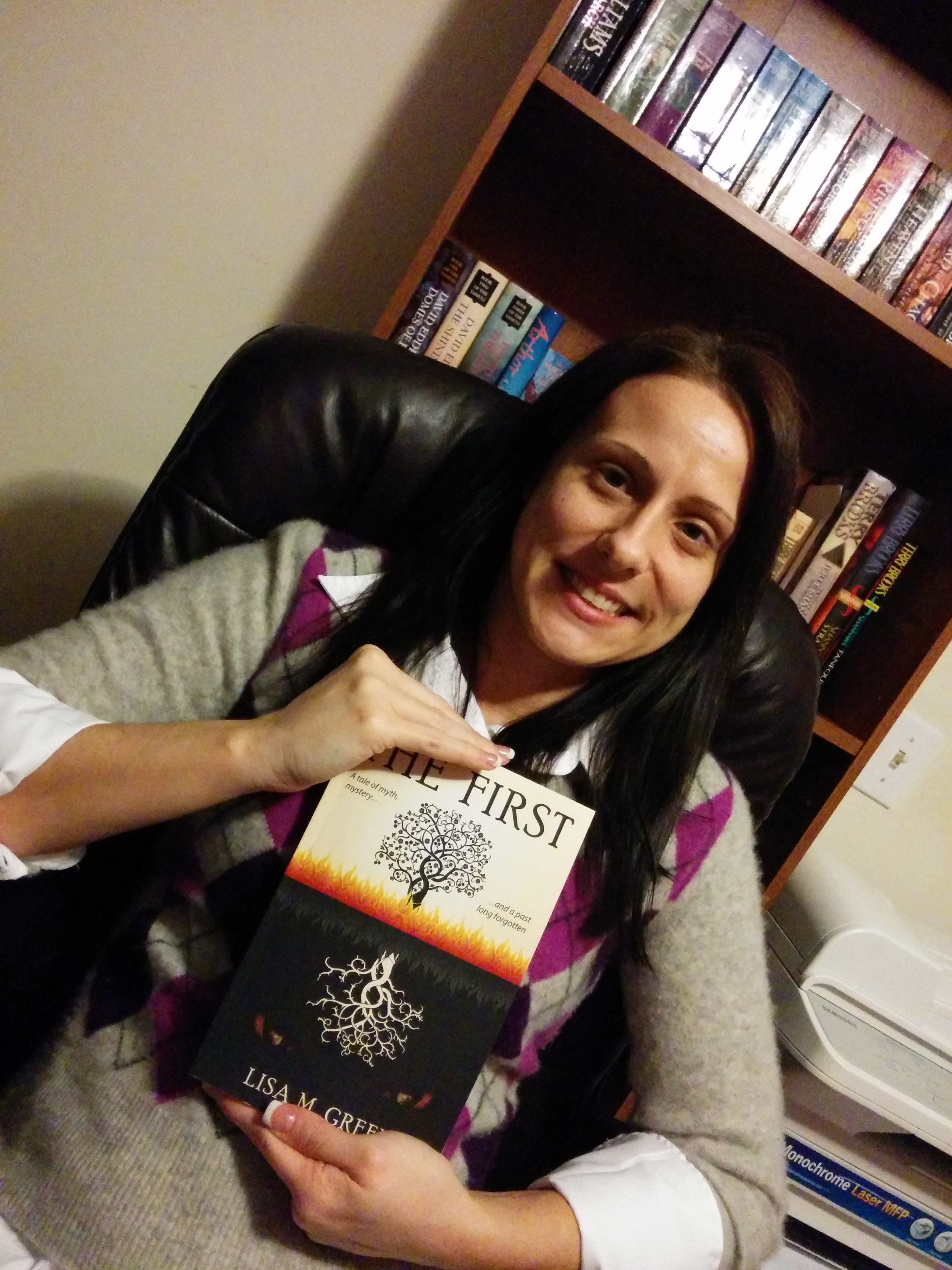 Lisa M. Green holding her book The First